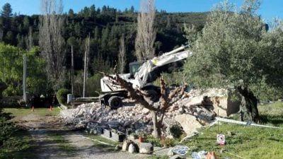 L'excavadora enderrocant la casa d'Alfara de Carles