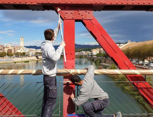 Alumnes del programa Treball als Barris repinten el Pont Roig de Tortosa per esborrar grafitis